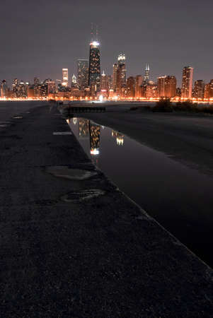 Chicago night skyline with partial beach and water reflections