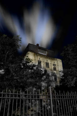 dreamscape: Haunted house with fence and dramatic night sky Stock Photo
