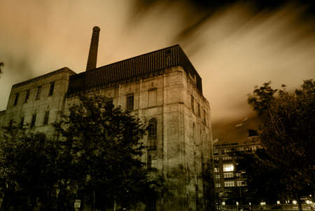 dream house: Old urban industrial building with dramatic night sky and clouds Stock Photo