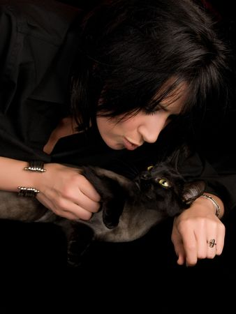 Attractive young woman playing with cute black kitten photo