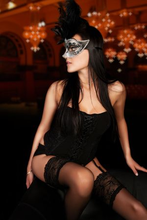 Sexy young woman in lingerie and mask in classic ballroom  Stock Photo