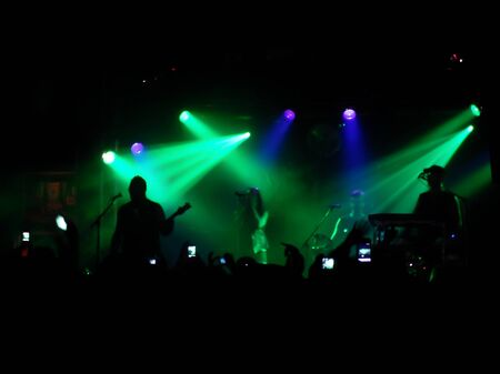 Backlit concert scene with band on stage photo