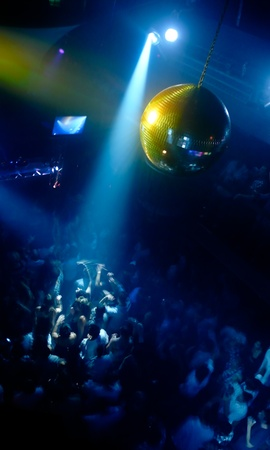 Nightclub scene with disco ball and dance floor crowd in motion photo