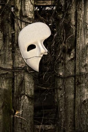 phantom: Masquerade - Phantom of the Opera Mask on Weathered Fence Stock Photo
