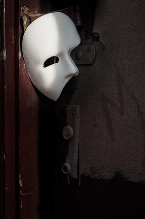 phantom: Masquerade - Phantom of the Opera Mask on Vintage Door Stock Photo