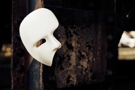 phantom: Masquerade - Phantom of the Opera Mask on Rusty Bridge Column Stock Photo
