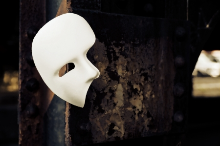 Masquerade - Phantom of the Opera Mask on Rusty Bridge Column Stock Photo