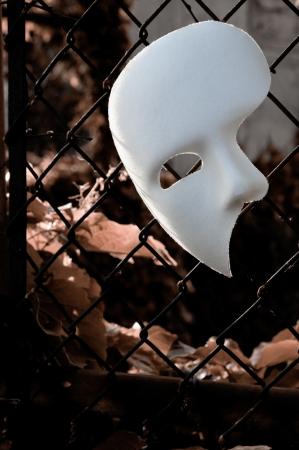 phantom: Masquerade - Phantom of the Opera Mask on Rusty Chainlink Fence Stock Photo