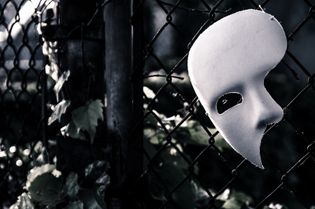 theatre masks: Masquerade - Phantom of the Opera Mask on Rusty Chainlink Fence Stock Photo