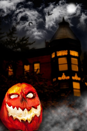 house party: Evil Pumpkin - Jack O Lantern in front of Haunted House Stock Photo