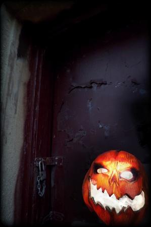 Evil Pumpkin - Jack O Lantern in front of Old Door photo
