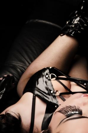 Dark Beauty - Sexy Woman in Lingerie liegen auf schwarzem Couch