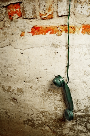 handset: Retro Phone Cord - Vintage Telephone Handset Receiver hanging by the Cord down a Brick Wall