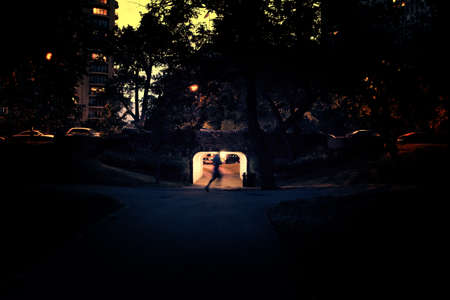 Person running past Dark City Bridge Underpass Sidewalk at Night