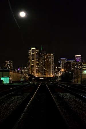 Moon over City Skyline and Train Tracks Stock Photo