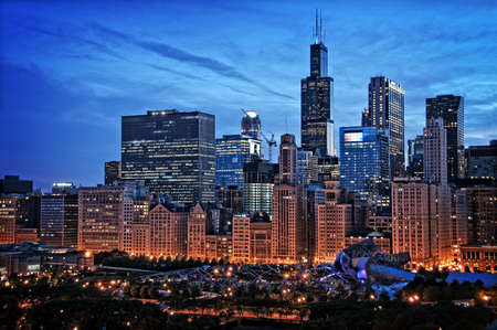 sears: Chicago lakefront skyline cityscape at night by millenium park with a dramatic cloudy sky.