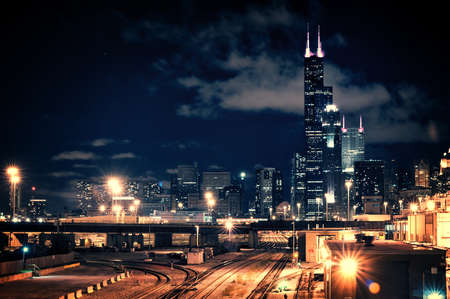 Chicago skyline cityscape at night featuring a train yard and urban bridge with a dramatic cloudy sky. Stock Photo