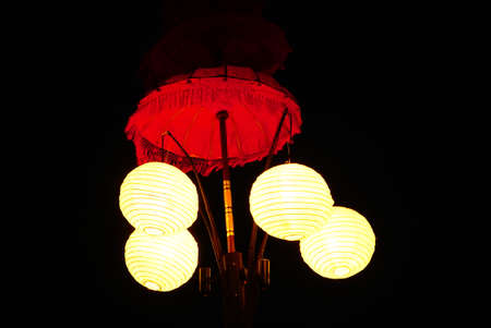 Red lamp shade with four light spheres on the black background. Outdoor. Bali. Indonesia.