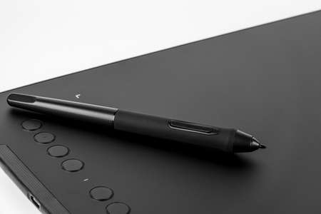 Black graphic tablet with pen for illustrators, designers and photographers, isolated on white background.