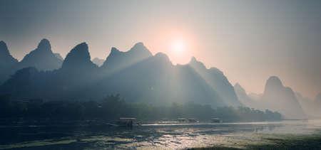 far east: Salida del sol detrás de las montañas Misty extraño en el río Lijiang en Guilin de China Guangxi