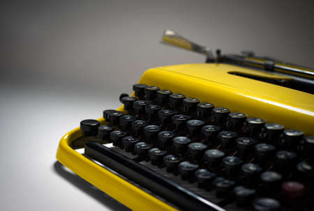 evocative: Vintage yellow typewriter in evocative spotlight and focus