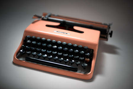 evocative: Vintage pink typewriter in evocative spotlight and focus