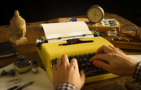 paper sculpture: Mans hands typing on a vintage typewriter on an yellow wooden desk - overwrite your text on the sheet Stock Photo