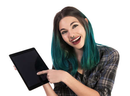 plaid shirt: Smiling and happy girl showing you something on a digital tablet on white background. Pierced, turquoise haired and dressing up a plaid shirt.