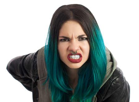 Angry fille percé regardant la caméra sur un fond blanc. Percées, turquoise aux cheveux et habiller une veste en cuir. Banque d'images