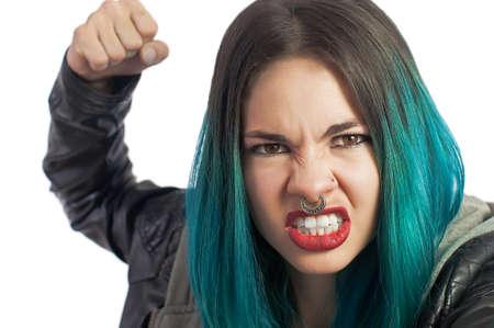 Angry fille percé poinçonnage droit contre la caméra sur un fond blanc. Turquoise couleur cheveux et veste en cuir.