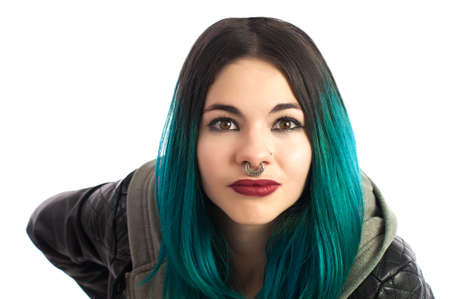 straight jacket: Beautiful pierced girl looking straight at camera on a white background. Pierced, turquoise haired and dressing a leather jacket.