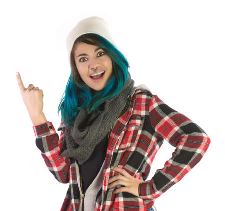plaid shirt: Beautiful smiling and amazed girl pointing upward on white background. Pierced, turquoise haired and dressing up a plaid shirt.