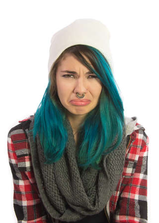 straight jacket: Sad and unhappy girl looking straight at camera. Pierced, turquoise haired and dressing up a plaid jacket and white cap.