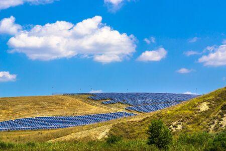 太陽電池パネル、青い空と白い雲と田園風景。