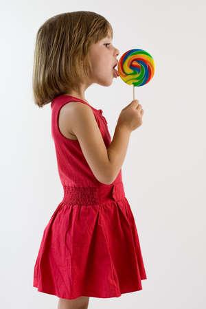 ロリポップを舐めている赤のドレスの少女