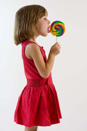 Little girl in red dress licking a lollipop photo