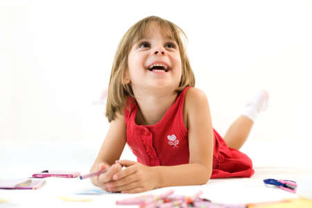 Smiling little girl in a red dress is laying with a crayon