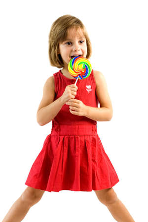 Little girl is standing and licking colorfull, wirl lollpop photo