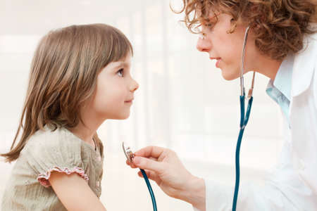 healing practitioners: Female mature doctor examining little girl
