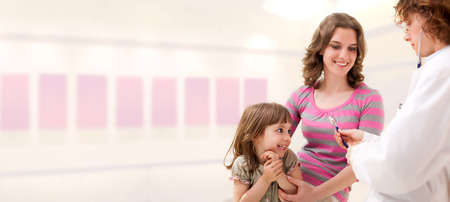 Female mature doctor examining little girl. Room for text. Stock Photo