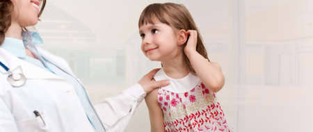 Female smiling doctor examining little girl.Room for text photo