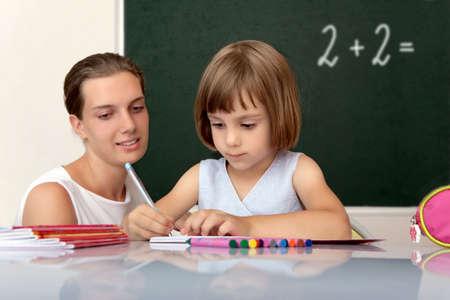 wiedererkennen: Grundschule Sch�ler arbeiten am Schreibtisch unter der Aufsicht eines Lehrers
