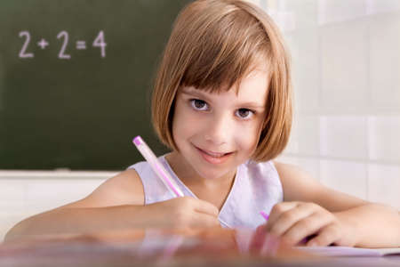 Portrait of a young pupil writing in a classroom  Stock Photo