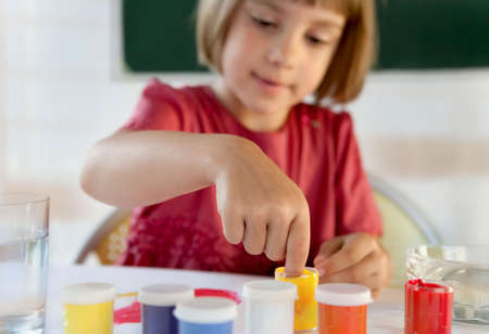 Schoolchild painting with hands in a classroom