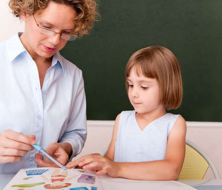 Little girl working under the supervision of a teacher Stock Photo