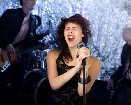 バック グラウンドでの彼女のバンドと美しいロック歌手 写真素材
