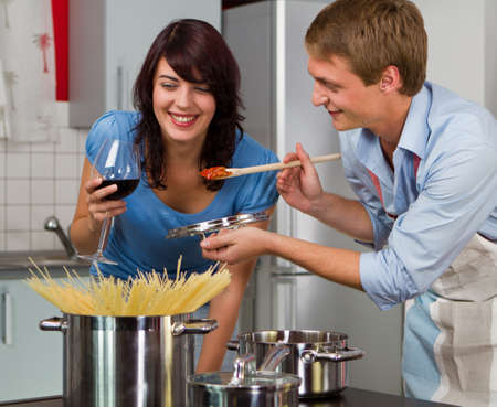 夕食調理キッチンで幸せな若いカップル