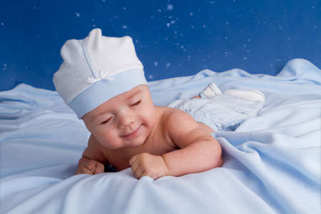 Cute baby lying on the blue blanket and sliping photo