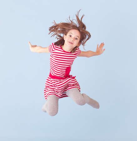 陽気な女の子、青い背景にジャンプ