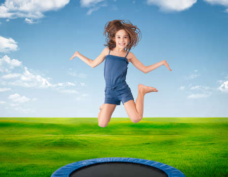cheerful girl jumping on a meadow on trampoline